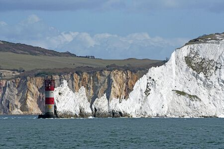 The Needles, Isle of Wight, England, UK. September 2019. The Needles lighthouse with helipad situated on the outermost chalk rocks. with a backdrop of the multi coloured sand cliffs of Alum Bay, Isle of Wight, UK