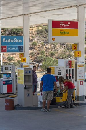 Agios Nikolaus, Crete, Greece. September 2019. Fuel filling station assistant filling a large petrol can for a customer, 報道画像