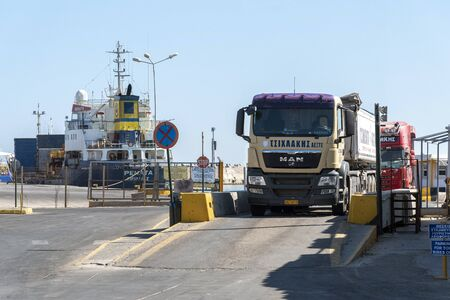 Rethymno, Crete, Greece. September 2019. Trucks entering and exiting the port at Rethymno, Crete, using the weighbridge for a weight check before and after loading from a ship alongside