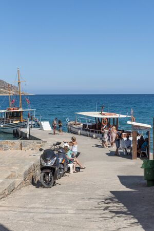 Plaka, Crete, Greece. October 2019.  Passengers wait to board a ferry to Spinalonga Island from a landing stage in Plaka, Crete, 報道画像