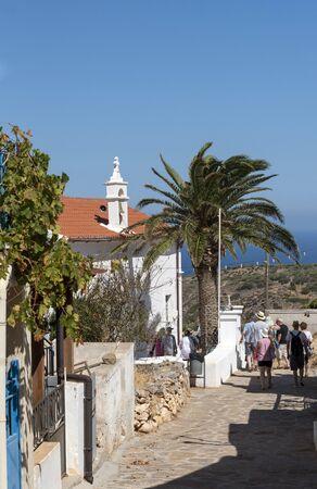 Kato Seles, northern Crete, Greece. October 2019.  Tourist group exploring a narrow lane in Kato Seles town centre.