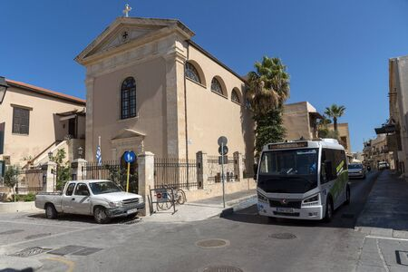 Rethymno, Crete, Greece. October 2019. A local bus passing a church in the t own centre of Rethymno, Crete,