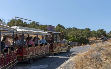 Seles, Northern Crete, Greece. October 2019.  A road train  and a group of tourists touring the Cretan area close to the mountain village of Seles.