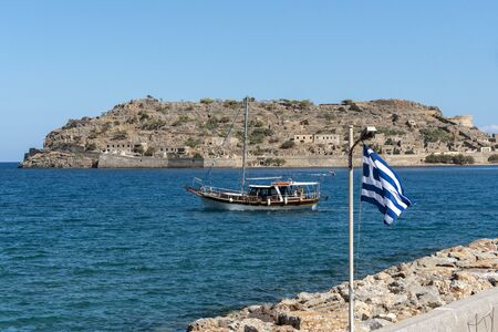 Spinalonga Island, northern Crete, Greece, October 2019. Ferryboats in Plaka with a backdrop of the former leper colony, Spinalonga Editorial