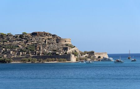 Spinalonga Island, Crete, Greece. October 2019. Ferries from Plaka and Elounda around the tiny harbour to transport tourists to visit this former leper colony.