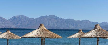 Agios Nikolaos, eastern Crete, Greece. October 2019.  Straw sun umbrellas and distance mountains at Agios Nikolaos, Eastern Crete, Editorial