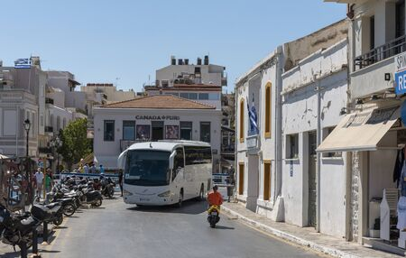 Agios Nikolaus, northern Crete, Greece. October 2019. Tour bus on the waterfront area of the town centre of this popular holiday resort.