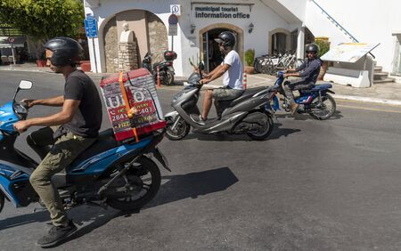 Agios Nikolaus, northern Crete, Greece. October 2019. Scooter riders near the Touist Office on the waterfront of this popular town. Editorial