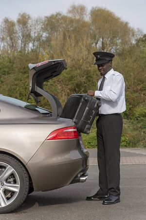 Andover, Hampshire, UK. October 2019.  A smartly dressed chauffeur, loading luggage into boot of a luxury car.