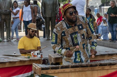 Cape Town, South Africa. Dec 2019. Zylophone player playing in a band busking on the waterfront central Cape Town.