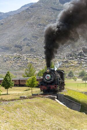 Ceres, Western Cape, South Africa. December 2019.  Steam engine hauling passenger coaches on the annual excursion to the Cherry Festival on Ceres golf estate. Background of mountains and Michells Pass.