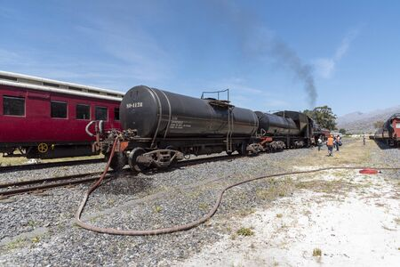 Ceres, Western Cape, South Africa. December 2019.  Diesel powered steam engine at the Cherry Festival on Ceres golf estate being replenished with water and checked before departing to Cape Tow`n Editorial