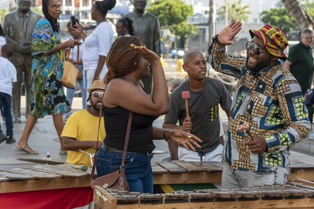 Cape Town, South Africa. Dec 2019. Zylophone player playing in a band busking on the waterfront high five's with an audience member. Cape Town.