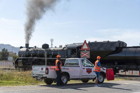 Wolseley, Swartland region, South Africa. Dec 2019. Man with red flag holds traffic. Steam train, diesel powered crossing highway at Wolseley. South Africa.
