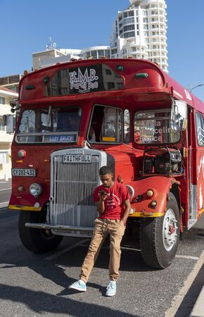 Strand, Western Cape South Africa. Dec 2019. Vintage fun and party red bus at Strand a populat seaside resort in the Western Cape, South Africa. Young man using mobile phone.