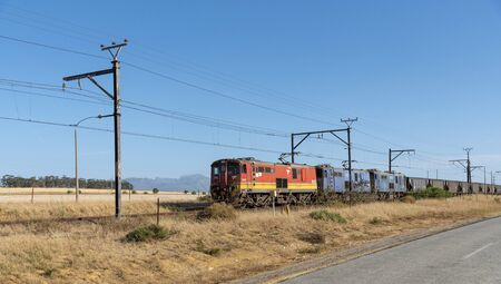 Hermon, Swartland, South Africa. December 2019. A South African freight train hauling wagons approaching Hermon in the Swartland region of the Western Cape, South Africa.