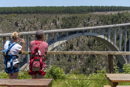 Bloukrans Bridge, Eastern Cape, South Africa. Dec 2019. Young couple wearing harnesses looking towards the arch on Bloukrans Bridge from where they will bungy jump.