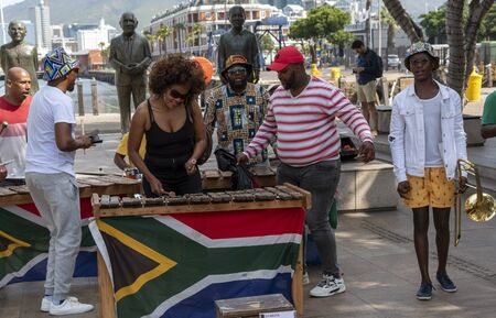 Cape Town, South Africa. December 2019. Street musician in revealing black top plays xylophone on the waterfront area of central Cape Town.