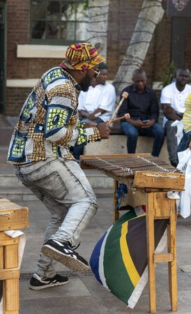 Cape Town, South Africa. December 2019. Street musician in colourful clothing plays xylophone on the waterfront area of central Cape Town.