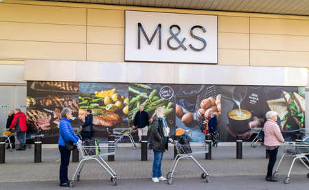 Southampton, England, UK. March 2020. Elderly people standing in line and six feet apart wait to enter a supermarket for the 'silver hour' shopping experience. During the Coronavirus scare. Social distancing in Hedge End, Southampton, UK Redactioneel