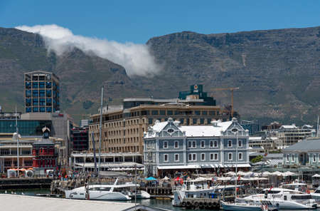 Cape Town, South Africa. 2019. Landcape view of the waterfront and cloud creeping over the summit of Table Mountain.