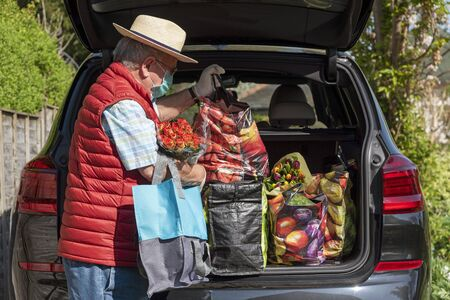 Elderly man wearing mask and gloves unloading the weekly shop and some colourful flowers from a car. During Covid-19. Stock Photo