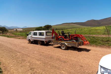 Overberg, Caledon, Western Cape, South Africa. 2019. Farm vehicle towing a trailer carrying a mini digger machine along a dirt road. Редакционное