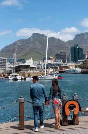Cape Town, South Africa. 2019. Young couple on the V&A Waterfront holding hands and admiring the view.