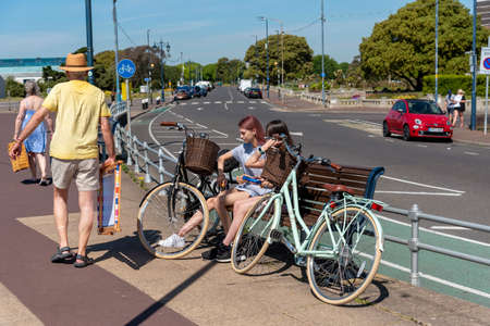 Southsea, Portsmouth, England, UK. 26 May 2020.  Cyclists sitting on a seat ignoring the government guidelines on social distancing not being 2 metres apart on the seafront in Southsea UK. Covid-19.
