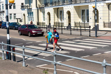 Southsea, Portsmouth, England, UK. 26 May 2020.   Social distancing not being observed. Not 2 metres apart on the seafront road in Southsea UK. Covid-19. Two boys wearing masks going to the beach. 에디토리얼