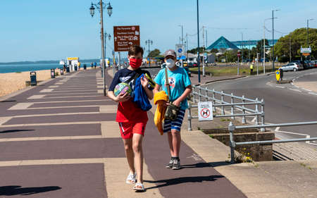 Southsea, Portsmouth, England, UK. 26 May 2020.   Social distancing not being observed. Not 2 metres apart on the seafront in Southsea UK. Covid-19. Two boys wearing masks.