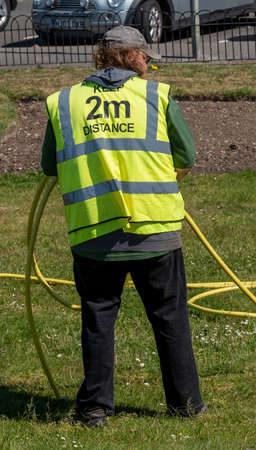 Southsea, Portsmouth, England, UK. May 2020. A municipal key worker wearing a reflective jack with the words, Keep 2m Distance during the Covid-19 outbreak. Editoriali