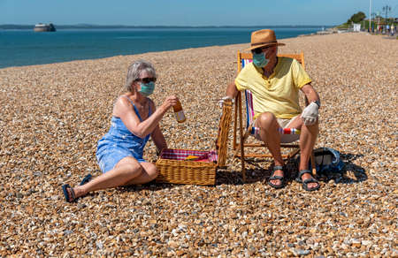 Southsea, Portsmouth, Southern England, UK. May 2020. Woman  wearing a surgical mask  social distancing from her husband during the Corvid-19 outbreak. Snacking on the beach in Southsea, UK.