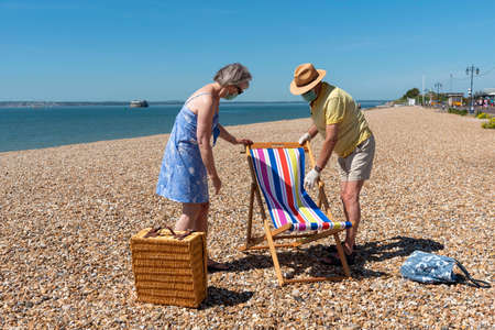 Southsea, Portsmouth, England, UK. May 2020. Elderly couple wearing medical masks erecting a deckchair on the beach at Southsea, UK.