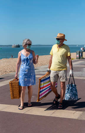 Southsea, Portsmouth, England, UK. May 2020. Elderly couple wearing medical masks carrying picnic equipment on the promenade at Southsea, UK. Editoriali