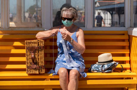Southsea, Portsmouth, England, UK. 2020, Woman sitting on a bench at the seaside knitting a woollen jumper during the Covid-19 lockdown.