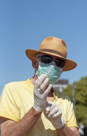 Man wearing a mask putting on medical rubber protective gloves during the Corvid-19 outbreak. On the beach in Southsea.