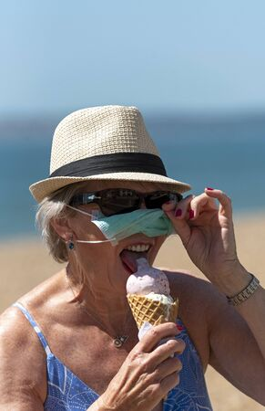 Woman eating ice cream whilst wearing a mask and rubber protective gloves during the Corvid-19 outbreak. On the beach in Southsea. Archivio Fotografico
