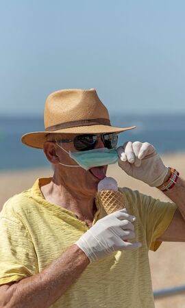 Man eating ice cream whilst wearing a mask and rubber protective gloves during the Corvid-19 outbreak. On the beach in Southsea.