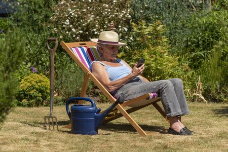 Hampshire, England, UK. 2020. Woman taking a break from the gardening by sitting in a deckchair on a hot summer day.