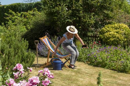 Woman taking a break from the gardening by sitting in a deckchair on a hot summer day.