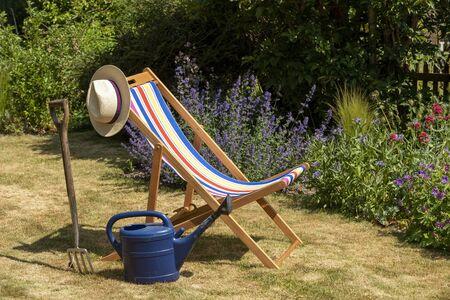 An open colourful deckchair in an English country garden.
