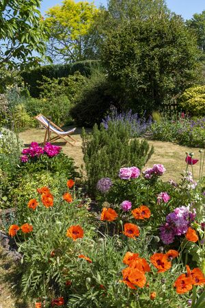 North Hampshire, England, UK. May 2020. An attractive English country garden and a deckchair in early summer. Hampshire, England UK. Archivio Fotografico