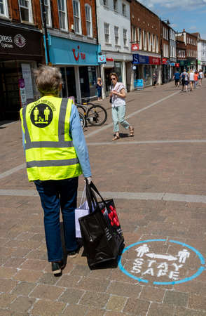 Newbury, Berkshire, England, UK. June 2020. Elderly woman shopper wearing a reflective jacket saying Please Keep Your Distance 2m. On the High Street in Newbury during Covid-19 outbreak Editoriali