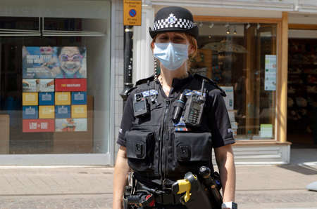 Newbury, Berkshire, England, UK. June 2020. A policewoman wearing a mask patrols the High Street in Newbury, Berkshire during the Covid-19 epidemic.