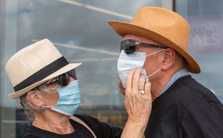 Hampshire, England, UK. 2020. Elderly couple during Covid-19 wife adjusting her husband's mask before entering a shop.