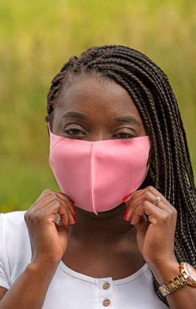 England, UK. 2020. Portrait of a black woman with braided hair style and wearing a pink coloured facemask during the Covid-19 outbreak