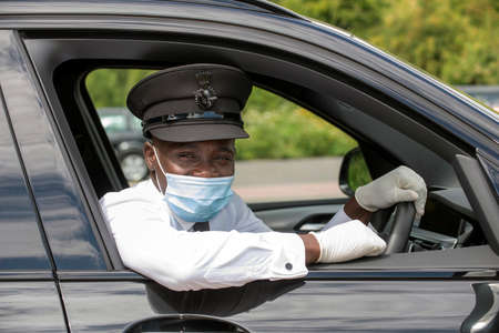 England, UK. 2020.  Chauffeur with uniform cap wearing a facemask during the Covid-19 outbreak