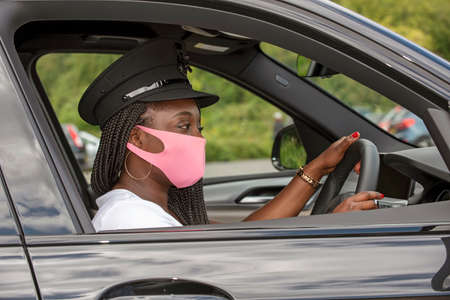 England, UK. 2020.  Woman chauffeur with uniform cap and braided hair wearing a facemask during the Covid-19 outbreak