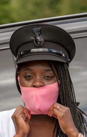 England, UK. 2020.   Portrait of a woman chauffeur with uniform cap and braided hair adjusting her pink coloured facemask during the Covid-19 outbreak